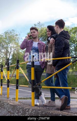 Deux jeunes garçons et une jeune fille se sont trouvés sur le lieu d'accord pour faire une promenade et intéressant Banque D'Images