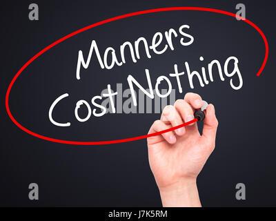 Man main écrit Manners Coût Rien avec marqueur noir sur l'écran visuel. Isolé sur le noir. Le commerce, la technologie, Banque D'Images