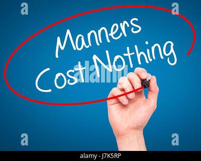 Man main écrit Manners Coût Rien avec marqueur noir sur l'écran visuel. Isolé sur le bleu. Le commerce, la technologie, Banque D'Images