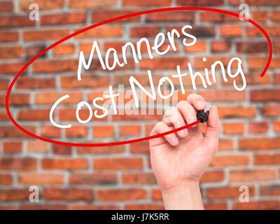 Man main écrit Manners Coût Rien avec marqueur noir sur l'écran visuel. Isolé sur des briques. Le commerce, la technologie, Banque D'Images