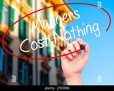 Man main écrit Manners Coût Rien avec marqueur noir sur l'écran visuel. Isolé sur la ville. Le commerce, la technologie, Banque D'Images