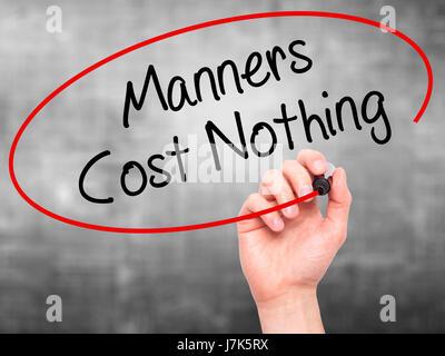 Man main écrit Manners Coût Rien avec marqueur noir sur l'écran visuel. Isolé sur le gris. Le commerce, la technologie, Banque D'Images