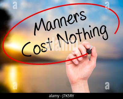 Man main écrit Manners Coût Rien avec marqueur noir sur l'écran visuel. Isolé sur la nature. Le commerce, la technologie, Banque D'Images