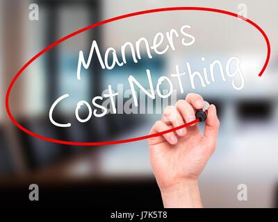 Man main écrit Manners Coût Rien avec marqueur noir sur l'écran visuel. Isolé sur bureau. Le commerce, la technologie, Banque D'Images
