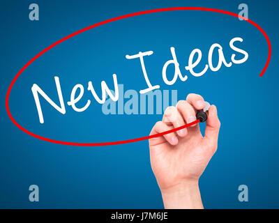 Man main l'écriture de nouvelles idées avec marqueur noir sur l'écran visuel. Isolé sur le bleu. Le commerce, la Banque D'Images