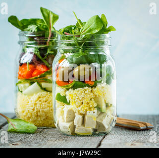 Salade colorée avec du couscous, le tofu et les légumes dans un bocal. L'amour pour une saine nourriture vegan concept Banque D'Images