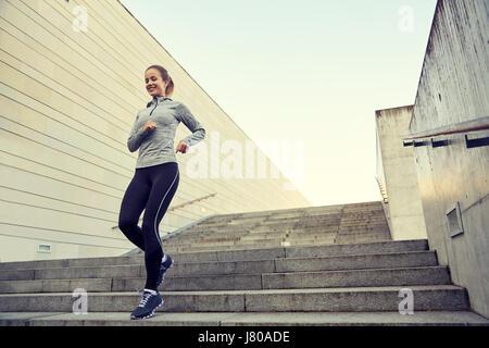 Happy sporty woman running au rez-de-ville