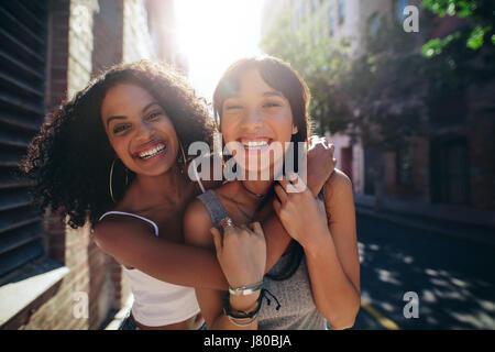 Portrait de deux jeunes femmes sur la rue de la ville d'avoir du plaisir. Amis de sexe féminin sur route embrassant Banque D'Images