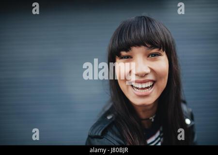 Close up portrait of young woman laughing contre fond gris. Belle hispanique modèle féminin s'amusant à l'extérieur. Banque D'Images
