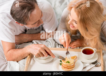 Heureux couple d'âge moyen ayant le petit déjeuner ensemble au lit Banque D'Images
