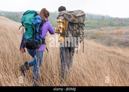 Vue arrière du jeune couple avec des sacs à dos se tenant la main et marcher dans l'herbe haute dans la campagne Banque D'Images