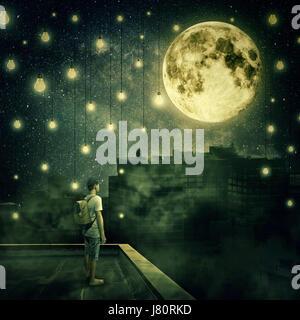 Jeune garçon rester sur le toit en regardant la pleine lune. Nuit Mystérieuse avec ampoules suspendues comme des Banque D'Images