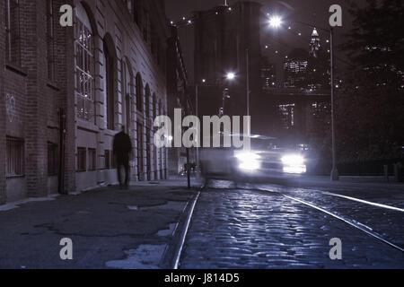 Nuit vanishing point vue vers le bas la rue Plymouth dans DUMBO, Brooklyn Bridge, longue exposition de fond avec Banque D'Images