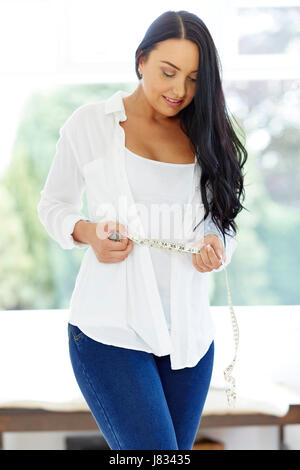 Woman ruban à mesurer autour de sa taille Banque D'Images