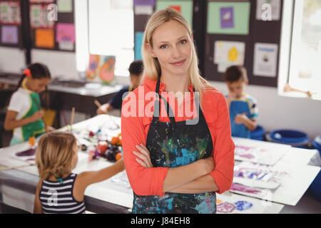 Portrait of smiling teacher standing with arms crossed en classe de dessin Banque D'Images