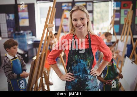 Portrait of smiling teacher standing hanche en classe de dessin Banque D'Images