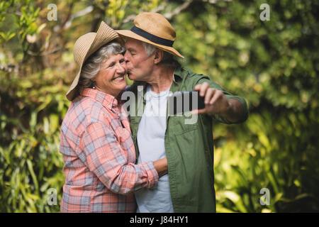 Man kissing woman tout en tenant contre des plantes selfies Banque D'Images