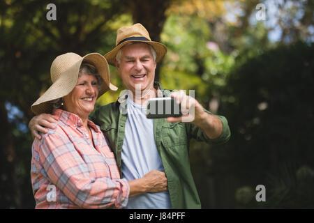 Happy senior couple prenant en selfies téléphone mobile en yard Banque D'Images