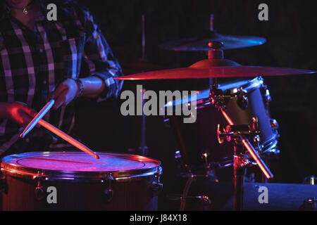 Mid section of female drummer jouer drum set in nightclub Banque D'Images