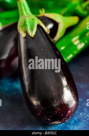 Violet Vert frais mûrs aubergines poivrons italien sur fond bleu foncé, une saine alimentation concept, ingrédients Banque D'Images