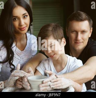 Travail Famille poterie sur roue. Beau père et belle mère montrant leurs processus fils de pot en argile création Banque D'Images