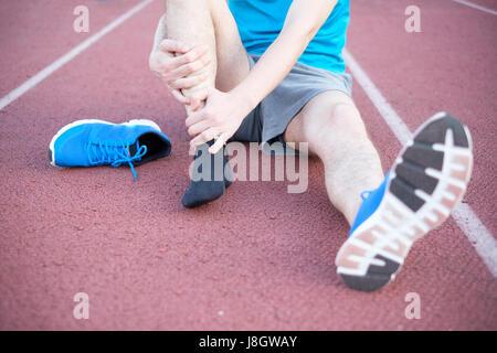 L'athlète exécute la sensation de douleur après une blessure à la cheville Banque D'Images