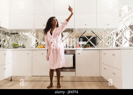 Jolie jeune femme noire avec de longs cheveux bouclés debout dans la cuisine et faire. selfies Femme portant un Banque D'Images