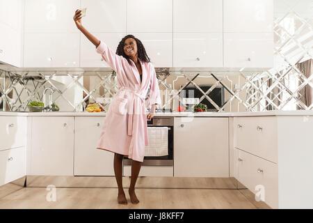Happy black woman en selfies la cuisine. Femme portant un peignoir rose et a de longs cheveux bouclés. Banque D'Images