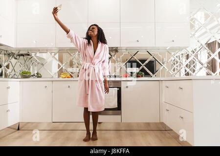Sourit african american woman en selfies la cuisine. Femme portant un peignoir rose. Banque D'Images