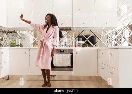 Jolie happy black femme debout dans la cuisine et faire. selfies Femme portant un peignoir rose et a depuis longtemps Banque D'Images