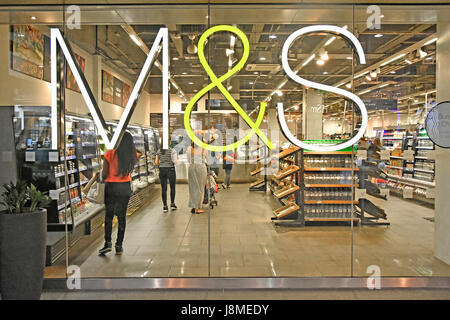 M&S M & S affiche montée sur une fenêtre en verre du magasin Foodhall Marks and Spencer du centre commercial Westfield avec des clients qui font leur magasin de produits alimentaires à Londres