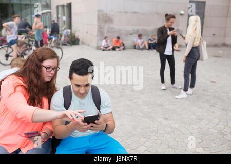 Groupe d'amis qui jouent le jeu de la réalité augmentée avec les téléphones mobiles