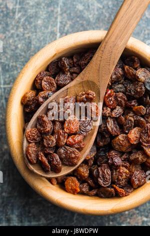 Raisins secs doux en cuillère en bois sur la vieille table de cuisine. Vue d'en haut. Banque D'Images