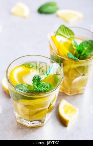 Citron glacé maison thé sucré à la menthe sur la table gris clair, rafraîchissements délicieux boisson d'été Banque D'Images