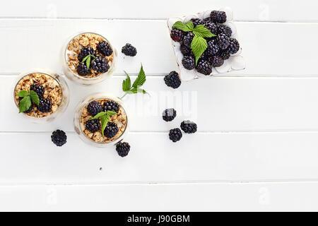 Les parfaits Blackberry fait avec du yaourt grec, granola et mûres fraîches tourné depuis plus de table en bois Banque D'Images