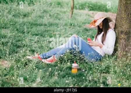 Femme de détente avec téléphone, sous arbre. Photo film ressemble Banque D'Images
