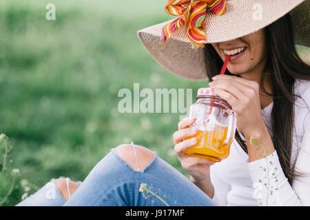 Femme de détente et de boire du jus d'orange froid. Photo film ressemble Banque D'Images