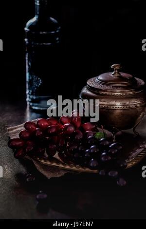 Nature morte avec raisins et bouteille dans clair de lune Banque D'Images