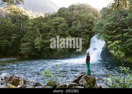 Female hiker debout sur la pierre, cascade de forêt, chutes, brûlures Iris Kepler Tack, Fiordland National Park, Southland