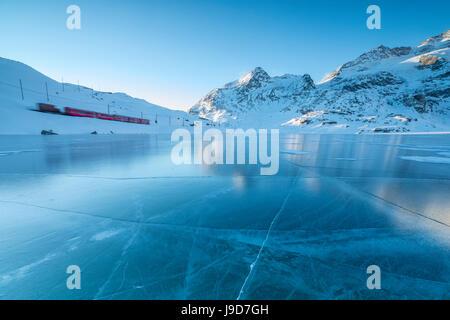 Le Bernina Express train passe à côté du lac gelé Bianco, col de la Bernina, canton des Grisons, Engadine, Suisse, Europe