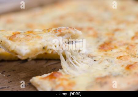 Servir une pizza quatre fromages avec fromage fondu Banque D'Images