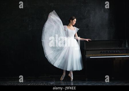 Jeune et incroyablement belle ballerine est de poser dans un studio noir Banque D'Images