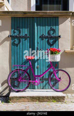 Vélo rose avec blanc panier plein de fleurs debout près de la porte bleue en bois ancien Banque D'Images