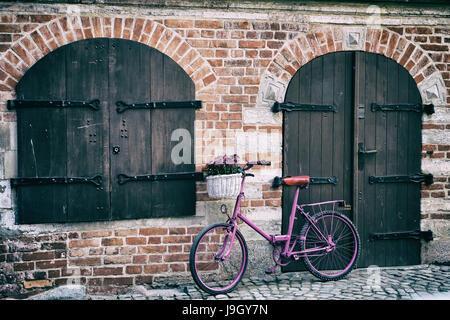 Vélo rose avec blanc panier plein de fleurs debout près du mur à côté de la fenêtre et porte en bois Banque D'Images