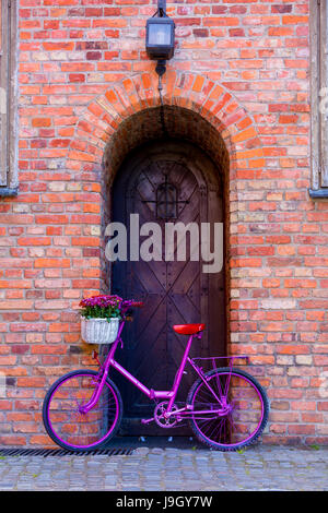 Vélo rose avec blanc panier plein de fleurs debout près du mur à côté de la vieille porte en bois Banque D'Images