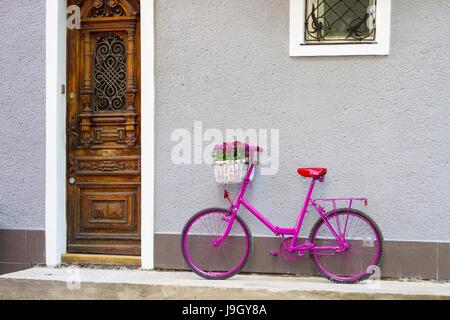 Vélo rose avec blanc panier plein de fleurs debout près du mur, près de la vieille porte en bois Banque D'Images