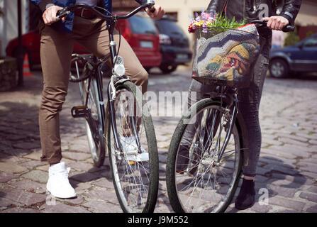 La section basse du couple standing avec des vélos sur street Banque D'Images