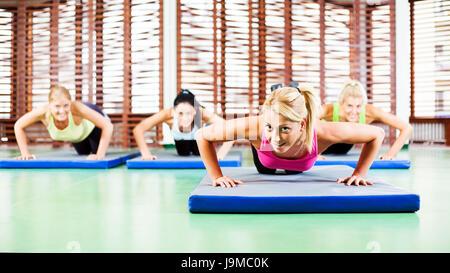 Les jeunes femmes exerçant dans la salle de sport, faire des pompes Banque D'Images