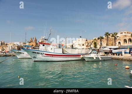 Bateaux de pêche maltais traditionnel peint de couleurs vives, dans le port de Marsaxlokk à Malte Banque D'Images