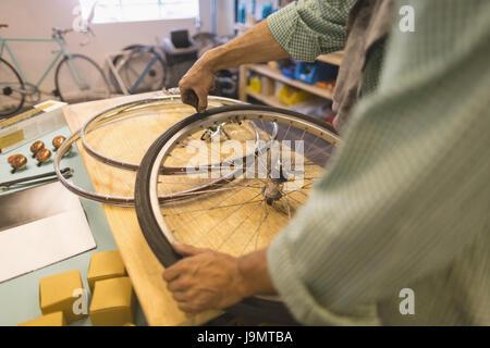 La réparation des travailleurs des roues sur le tableau à l'atelier vélo vintage Banque D'Images